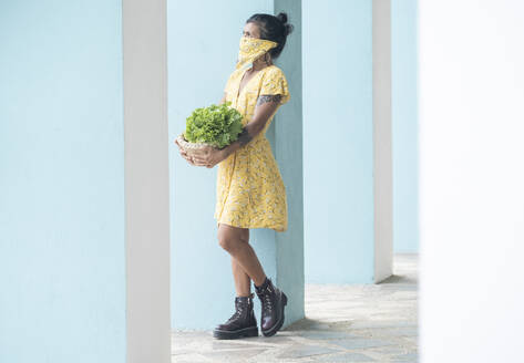 Woman wearing mouth cloth holding basket with salad and fresh fruits - AMUF00038