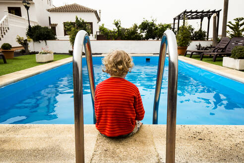 Back view of little boy sitting in front of a swimming pool - IHF00314