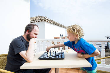 Father and son playing chess on roof terrace, Spain - IHF00317