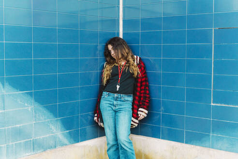 Teenage girl leaning at tiled blue wall outdoors - ERRF02962