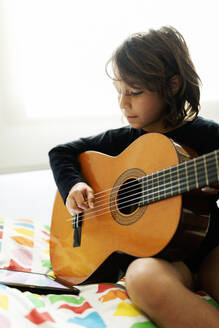 Boy sitting on bed using digital tablet for playing song on guitar - VABF02689