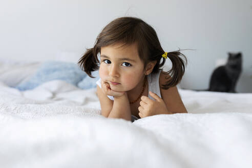 Portrait of little girl lying on bed - VABF02710