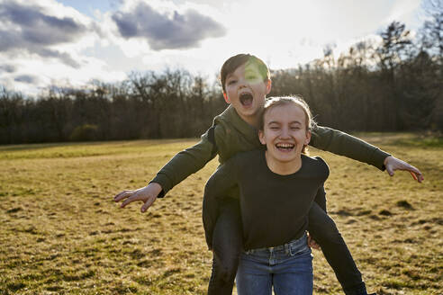 Happy girl carrying brother piggyback on a meadow - AUF00278