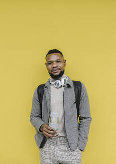 Portrait of stylish man with reusable cup and headphones in font of a yellow wall - AHSF02117