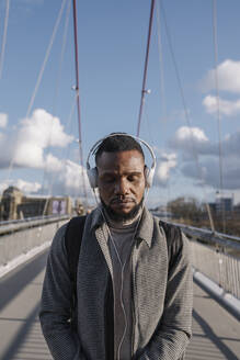 Portrait of stylish man on a bridge with headphones listening to music with closed eyes - AHSF02156
