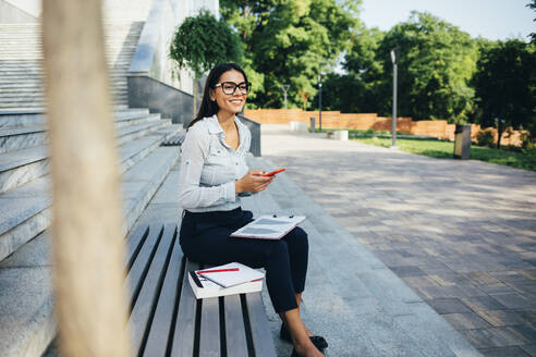 Businesswoman using smartphone and sitting on a bench in a park - OYF00117