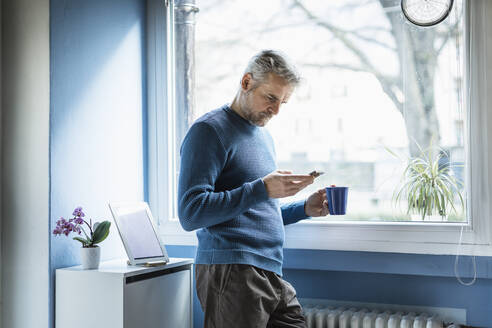 Mature man standing with coffee mug standing in living room looking at smartphone - MCVF00250