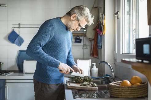 Mature man preparing artichokes in his kitchen - MCVF00253