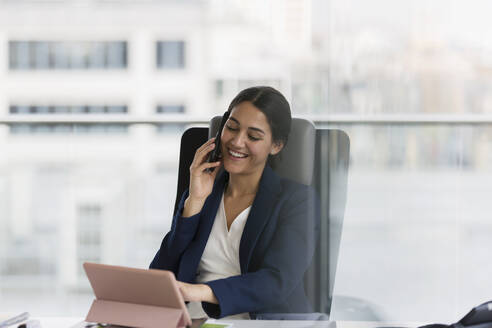Smiling businesswoman talking on smart phone in office - CAIF25624