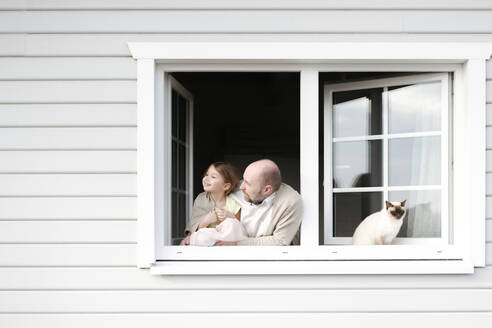 Mature man with smiling daughter and cat leaning out of window of his house - VYF00113