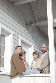 Portrait of family on porch of their house - VYF00128