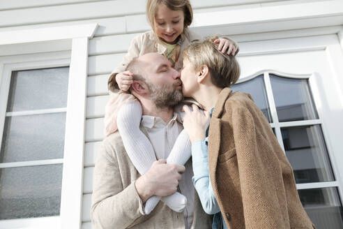 Happy family hugging and kissing in front of their house - VYF00131