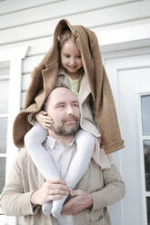 Portrait of father with daughter on his shoulders in front of their house - VYF00137