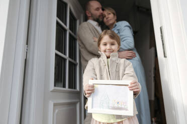 Happy little girl with drawing of her house and parents hugging behind her - VYF00140