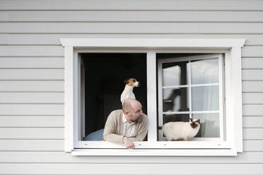 Mature man with cat and dog leaning out of window of his house - VYF00143