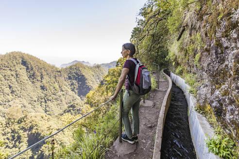 Portugal, Madeira, Ribeiro Frio, Female backpacker admiring surrounding landscape from viewpoint along Levada do Furado - WDF05921