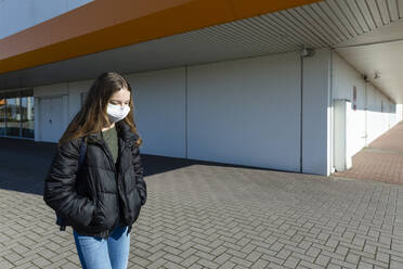 Girl with mask walking outside at closed shopping center - OJF00365