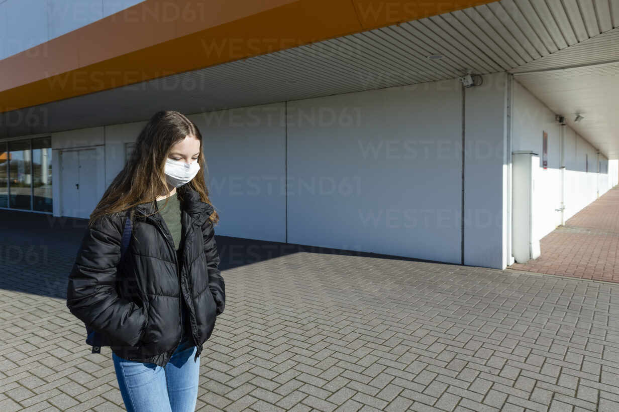 Girl with mask walking outside at closed shopping center - OJF00365 - Julia Otto/Westend61