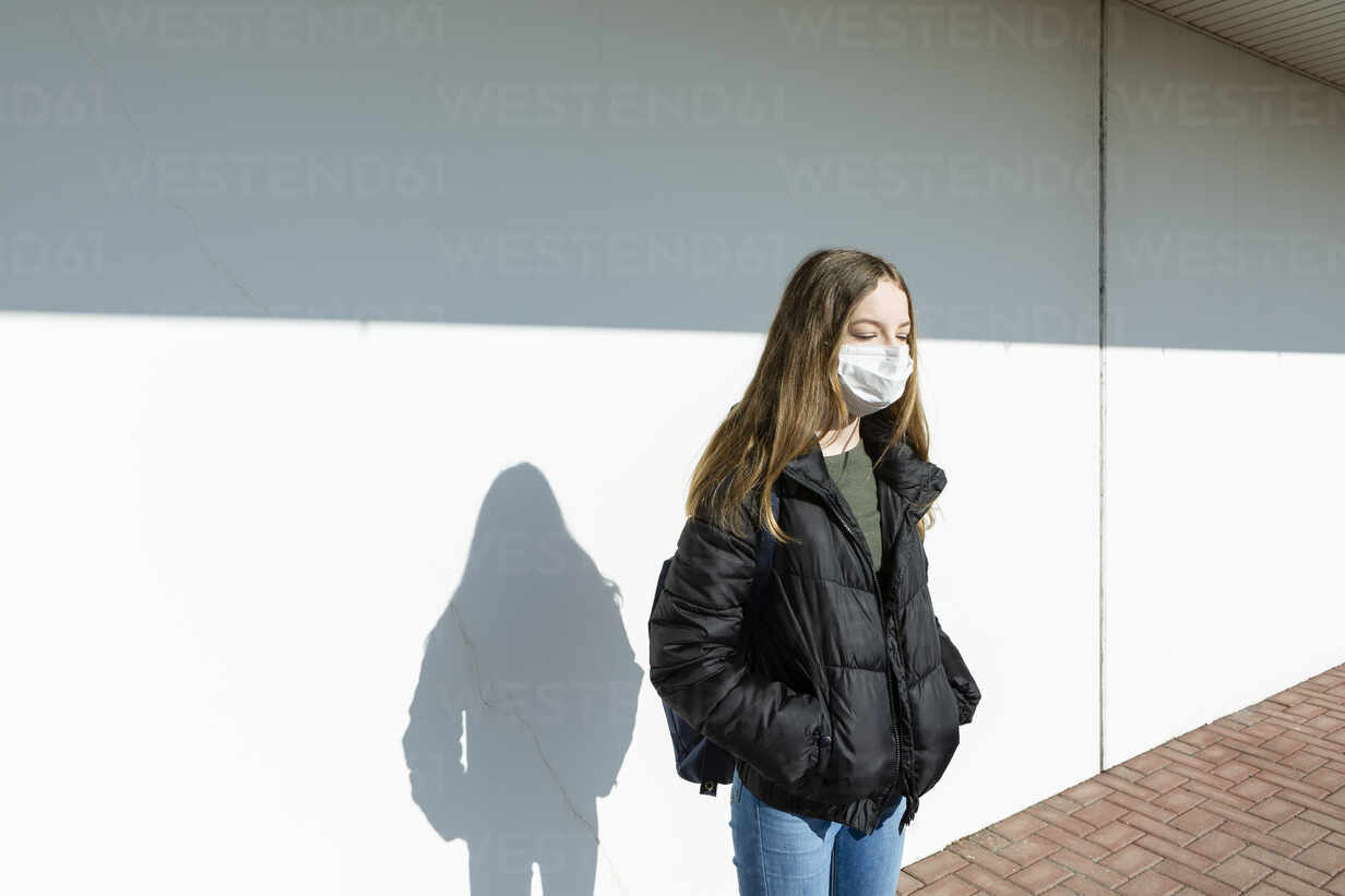 Girl with mask standing in front of a wall - OJF00368 - Julia Otto/Westend61