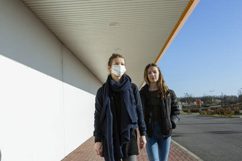 Woman wearing face mask walking with daughter at an empty street - OJF00377