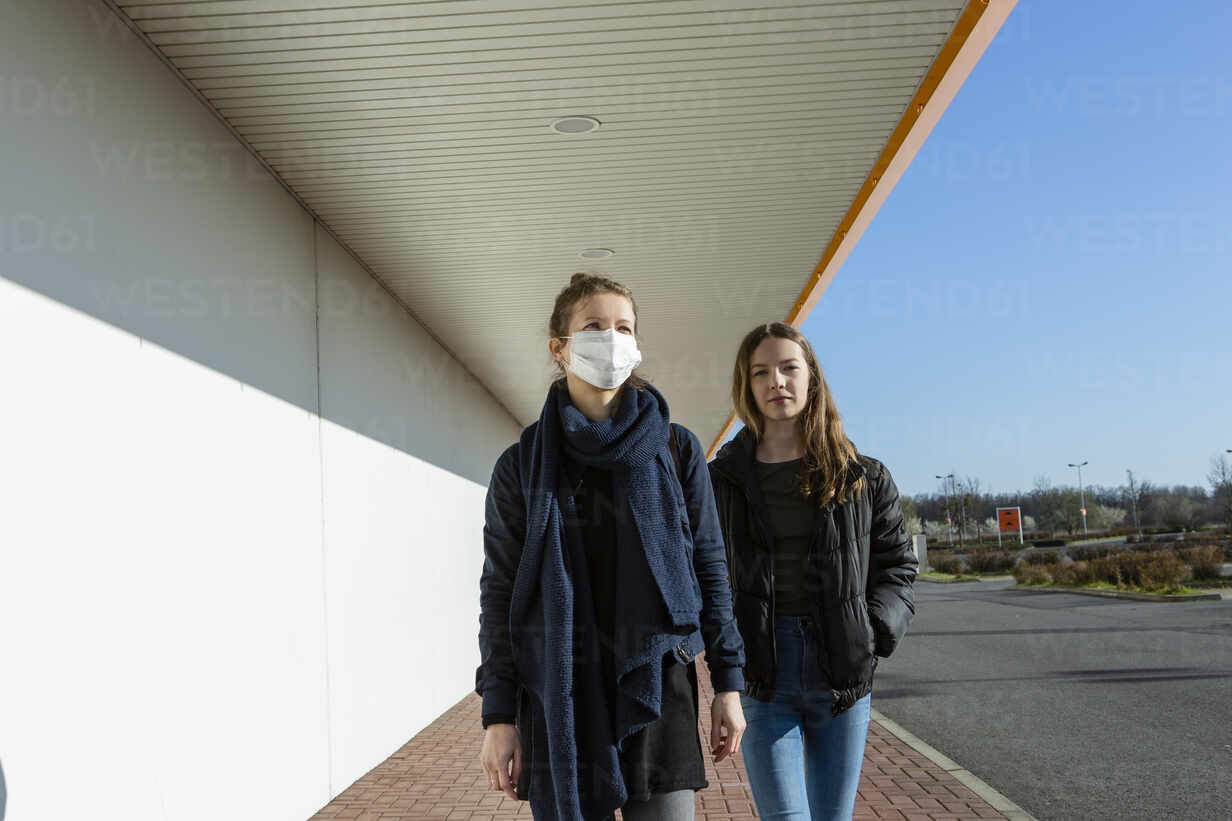 Woman wearing face mask walking with daughter at an empty street - OJF00377 - Julia Otto/Westend61