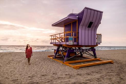 Woman at Art Deco lifeguard hut on Miami Beach at sunset, Miami, Florida, USA - DAWF01283