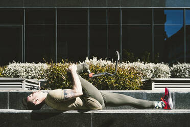 Disabled athlete with leg prosthesis lying on a wall stretching - DAMF00297