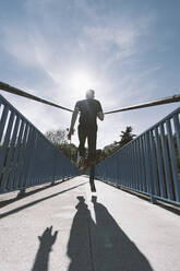Rear view of disabled athlete with leg prosthesis running on a bridge - DAMF00306