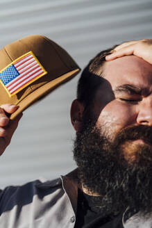Bearded man with baseball cap with American flag wiping off sweat from his head - JCMF00555