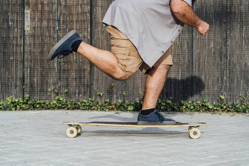 Crop view of mature man skateboarding - JCMF00558