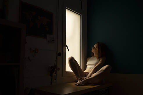 Serious young woman sitting on windowsill at home looking out - AFVF05945
