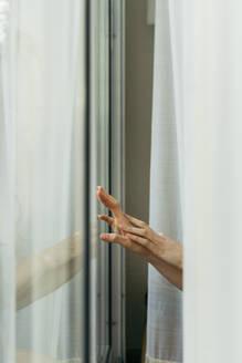 Hand of a woman touching windowpane - AFVF05957