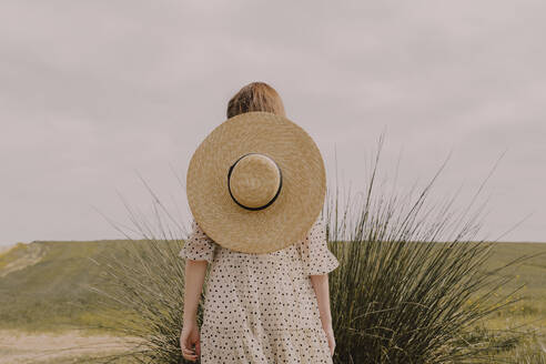Woman with straw hat and vintage dress alone at a remote field in the countryside - ERRF03063