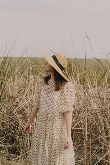 Woman with straw hat and vintage dress alone at a remote field in the countryside - ERRF03114
