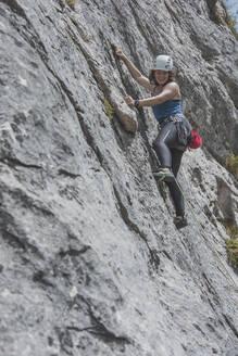 Female mountain climber climbing rock face - FVSF00026