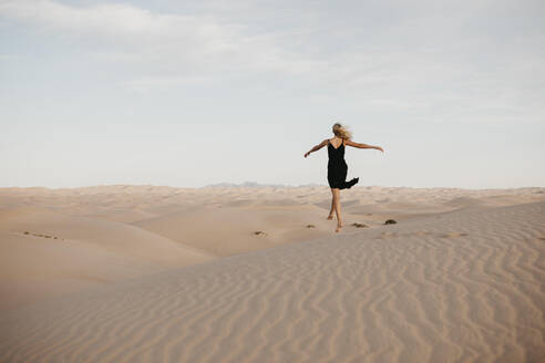 Back view of blond woman jumping in the air, Algodones Dunes, Brawley, USA - LHPF01215