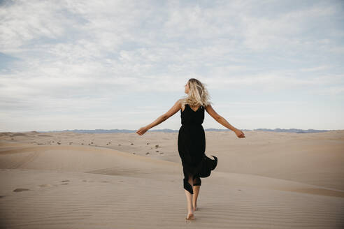 Back view of blond woman walking barefoot on sand dune, Algodones Dunes, Brawley, USA - LHPF01218