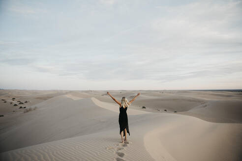 Back view of blond woman standing on sand dune raising hands, Algodones Dunes, Brawley, USA - LHPF01224