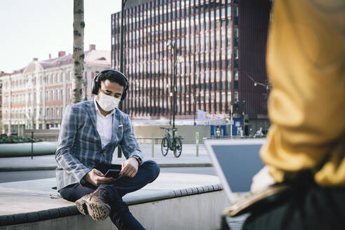 Businessman wearing face mask sitting outside using smartphone - MASF17329