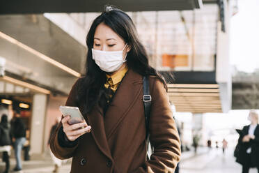 Woman walking in street with face mask using smartphone - MASF17344