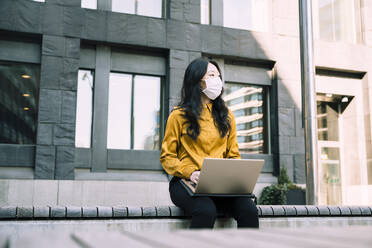 Businesswoman with laptop working outside wearing face mask - MASF17362