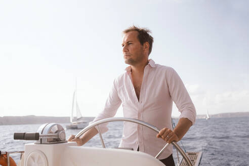 Confident mature man sailing catamaran with helm on sea against sky - MASF17422
