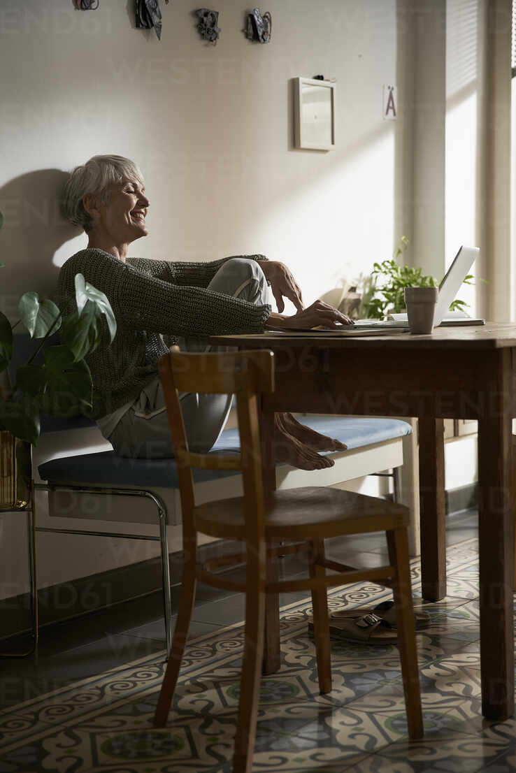 Happy Senior Woman Sitting On Bench In Her Kitchen Using Laptop Stockphoto