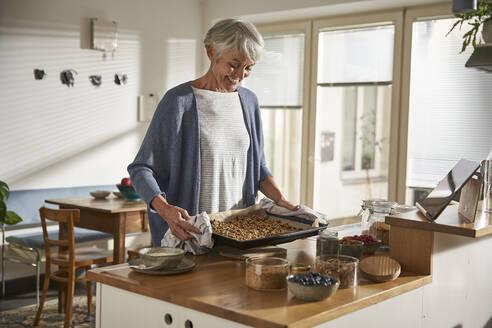 Smiling senior woman preparing granola - AUF00310
