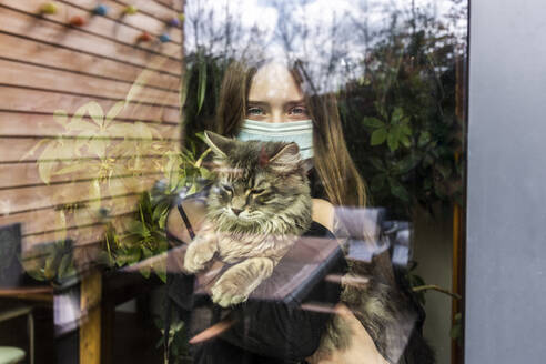Portrait of girl with surgical mask and cat behind window pane - SARF04515