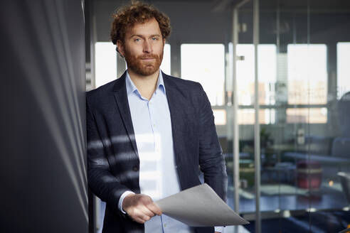 Portrait of confident businessman holding papers in office - RBF07300