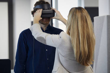 Businesswoman applying VR glasses on businessman in office - RBF07327