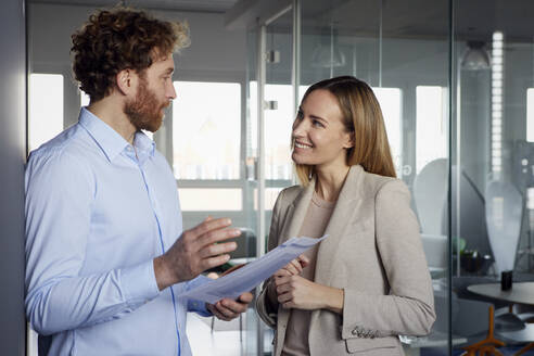 Businessman and businesswoman working together on papers in office - RBF07339