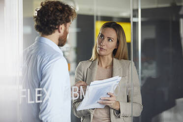 Businessman and businesswoman working together on papers in office - RBF07345