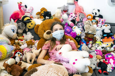 Girl with face mask, sitting on couch, covered in cuddly toys - SARF04516